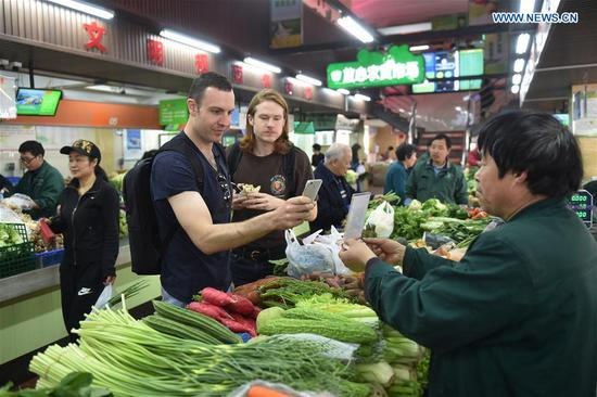Tim Clancy (L Front), an Australian who has lived in Hangzhou for six years with his Chinese wife, takes his American friend to buy vegetables through mobile payment at a market in Hangzhou, capital of east China's Zhejiang Province, April 14, 2017. Tim took his American friend to make a cash-free travel for one day in Hangzhou, with mobile phones being used to pay all of their costs. Dubbed the world's largest mobile payment city, more than 98 percent of Hangzhou's taxis, over 95 percent of supermarkets and convenience stores, and more than 50 percent of restaurants in Hangzhou have access to mobile payment services. With smartphones, tourists in Hangzhou can use mobile payment service when shopping, dining, or calling a cab. (Xinhua/Huang Zongzhi)