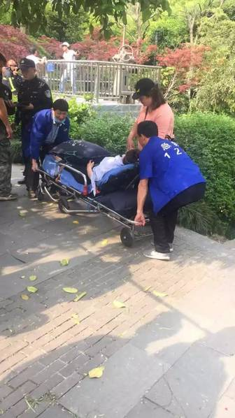 A young woman lay on a stretcher by the lake was suspected to be the mother of the child. She was carried away by the ambulance later.