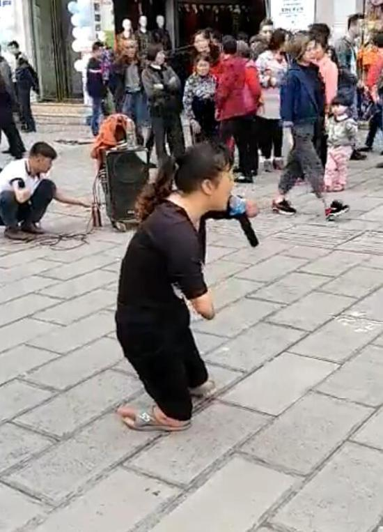 Nie Xiangzhi performs singing on the street.