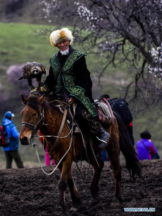 An old man in traditional costume rides on a horse in