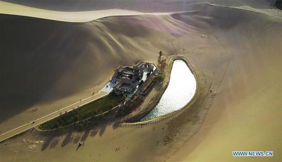 Photo taken on April 16, 2017 shows the Crescent spring and Mingsha Mountain (Singing Sand Dune) scenic site before sunset in Dunhuang, northwest China's Gansu Province. (Xinhua/Fan Peishen)