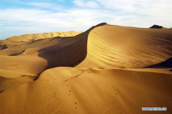 Photo taken on April 16, 2017 shows the Mingsha Mountain (Singing Sand Dune) scenic site before sunset in Dunhuang, northwest China's Gansu Province. (Xinhua/Fan Peishen)