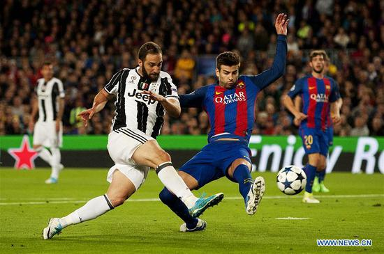 Juventus's Gonzalo Higuain (L) vies with Barcelona's Pique during the UEFA Champions League quarter final second leg match between FC Barcelona and Juventus FC at the Camp Nou Stadium in Barcelona, Spain, April 19, 2017. The match ended 0-0 tie. Juventus advanced to the semifinal with 3-0 on aggregate. (Xinhua/Lino De Vallier)