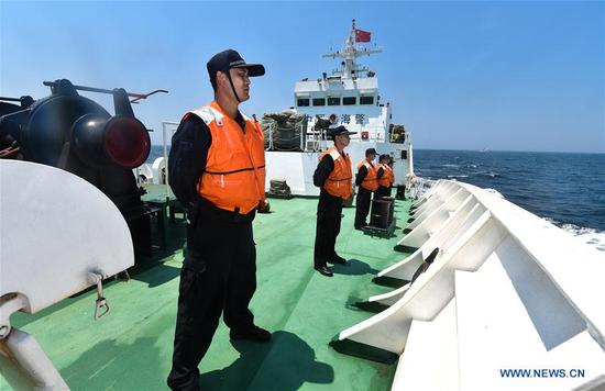 Crew members stand onboard a Chinese police vessel during a China-Vietnam joint fishery inspection in the Beibu Gulf, April 20, 2017. China and Vietnam concluded a 3-day joint fishery inspection in the Beibu Gulf on Thursday. (Xinhua/Mao Siqian)