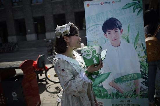 """This picture taken on April 14, 2017 shows a woman handing out leaflets during an event for fans of China's boy band sensation TFBoys """"The Fighting Boys"""" at a university in Beijing. -- AFP"""