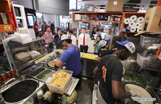 Staffs work at the kiosk of Mr. Bing in UrbanSpace food court in New York, the United States, April 17, 2017.