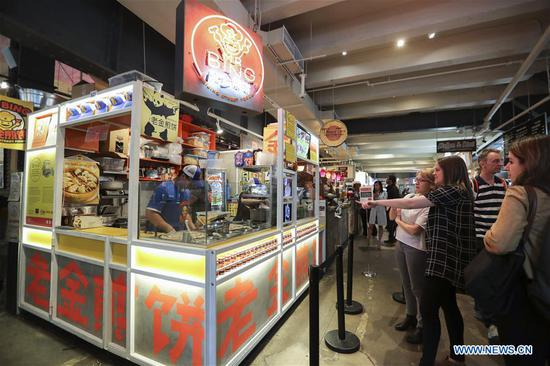 Customers select their favorite Jianbing at the kiosk of Mr. Bing in UrbanSpace food court in New York, the United States, April 17, 2017.