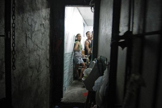 A dozen people have been found stuffed inside a closet-sized cell hidden behind a book shelf in a Philippine police station (AFP Photo/Vincent GO)