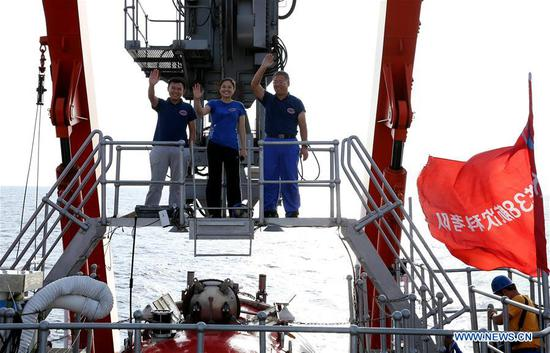 Crew members and scientists Tang Jialing, Zhang Yi and Shi Xuefa (L-R) wave after conducting a dive mission on board Jiaolong, China's manned submersible, in the South China Sea, south China, April 29, 2017. Jiaolong conducted its third dive Saturday in the South China Sea during the second stage of China's 38th ocean scientific expedition. Spending nine hours and thirty-five minutes in water, the maximum depth of the Jiaolong's work this time was 2,930 meters below sea level. (Xinhua/Liu Shiping)