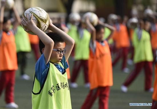 Students do football exercises on school playground in Hohhot, capital of north China's Inner Mongolia Autonomous Region, May 3, 2017. (Xinhua/Wang Zheng)
