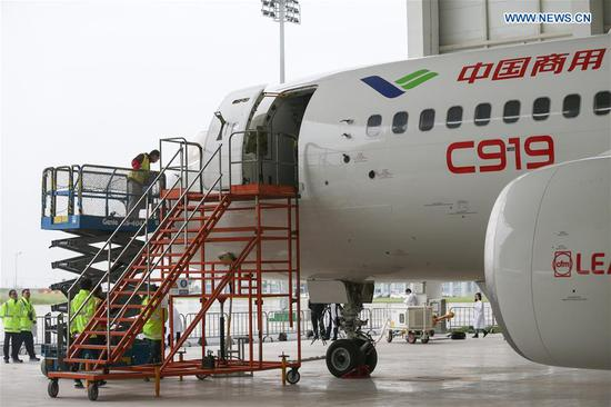 "Staff workers check a C919, China's first domestically-built large passenger jet, at a hangar of the Commercial Aircraft Corporation of China (COMAC) in Shanghai, east China, May 4, 2017. The maiden flight of the C919 is scheduled for May 5. The flight will depart from Shanghai Pudong International Airport. ""If weather conditions are not suitable, the maiden flight will be rescheduled,"" COMAC said. (Xinhua/Ding Ting)"
