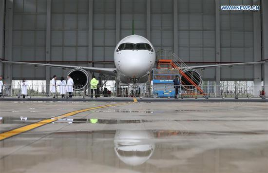 "Photo taken on May 4, 2017 shows a C919, China's first domestically-built large passenger jet, at a hangar of the Commercial Aircraft Corporation of China (COMAC) in Shanghai, east China. The maiden flight of the C919 is scheduled for May 5. The flight will depart from Shanghai Pudong International Airport. ""If weather conditions are not suitable, the maiden flight will be rescheduled,"" COMAC said. (Xinhua/Ding Ting)"