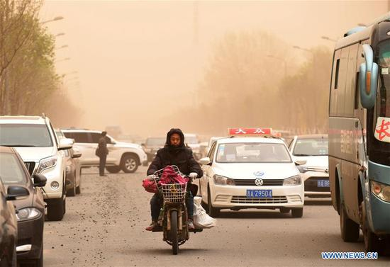 A resident rides a motorcycle amid sandstorm in Changchun, capital of northeast China's Jilin Province, May 6, 2017. A sandstorm and strong wind hit Changchun on Saturday. (Xinhua/Lin Hong)