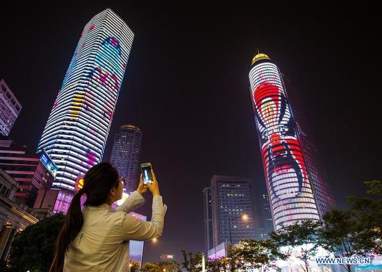 A citizen takes photos of a light show to greet the upcoming 8th China Peking Opera art festival, in the Xinjiekou area of Nanjing, capital of east China's Jiangsu Province, May 6, 2017. The art festival will be held in Nanjing from May 11 to 29. (Xinhua/Su Yang)