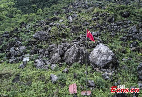 A flag flies at the former site of a school, buried by landslides in the 2008 Wenchuan Earthquake in Jingjiashan in Beichuan County, Wenchuan City, Southwest China's Sichuan Province. The magnitude 8.0 earthquake struck Wenchuan on May 12, 2008, leaving more than 80,000 people reported dead or missing. Nine years after the massive quake, Beichuan receives visitors who mourn the victims and researchers, who study seismology or emergency rescues. (Photo/VCG)