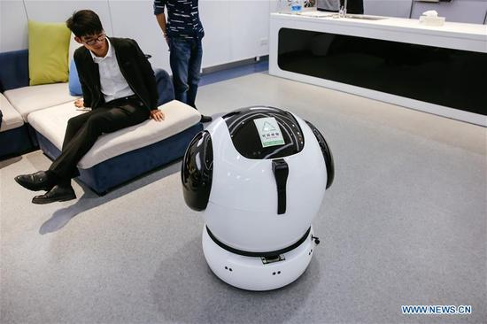 A visitor looks at an automatic trashcan during the fourth China Robot Summit in Yuyao, east China's Zhejiang Province, May 16, 2017. The two-day robot summit, displaying a variety of artificial intelligence technologies and service robots, kicked off here on Tuesday. (Xinhua/Zhang Cheng)