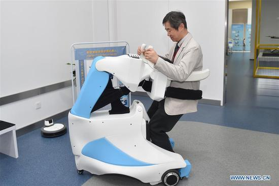 A visitor experiences an intelligent nursing robot in Yuyao, east China's Zhejiang Province, May 16, 2017. The two-day China Robot Summit, displaying a variety of artificial intelligence technologies and service robots, kicked off here on Tuesday. (Xinhua/Huang Zongzhi)