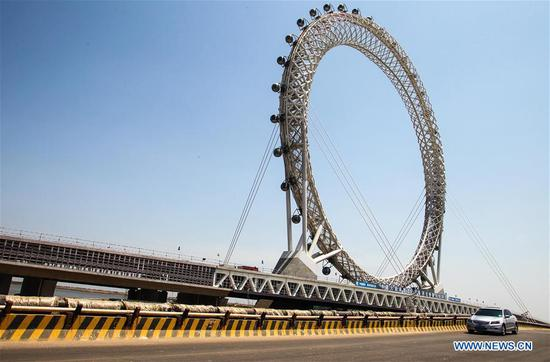 A car drives past a centerless ferris wheel in Weifang City, east China's Shandong Province, May 17, 2017. The ferris wheel, whose diameter is 125 meters, has a height of 145 meters. It is built according to the designing concept of kite and has 36 sight-seeing cabins. (Xinhua/Sun Shubao)