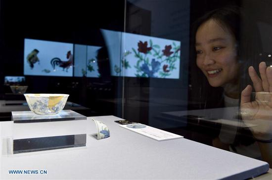 A visitor watches porcelain wares displayed at the Shandong Museum in Jinan, capital of east China's Shandong Province, May 18, 2017. Thursday marks the International Museum Day. (Xinhua/Guo Xulei)