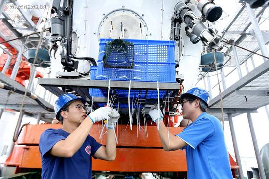 Scientists prepare the Jiaolong, China's manned submersible, on its mother ship Xiangyanghong 09, May 22, 2017. The ship arrived at the Mariana area Monday and started testing temperature, salinity and depth for Tuesday's dive in the Mariana Trench, the first of the expedition's third stage. (Xinhua/Liu Shiping)