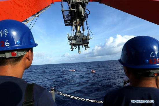 Staff members watch the frogmen and Jiaolong, China's manned submersible, before a dive in the Mariana Trench on May 25, 2017. Jiaolong conducted the second of its five dives in the third stage of China's 38th oceanic expedition on Thursday. (Xinhua/Liu Shiping)