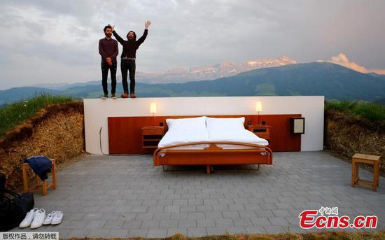 Swiss artists Frank and his twin-brother Patrik Riklin (R) pose in their Null-Stern-Hotel (Zero-star-hotel) land art installation on an alp in front of the peak of mount Saentis near Gonten, Switzerland June 1, 2017. Guests can order overnight stays in the Null-Stern-hotelroom with no walls and roof located on some 1,200 metres altitude in the eastern Swiss Alps. (Photo/Agencies)