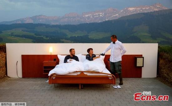 Raphael (LtoR) and Mirjam receive a drink from butler Koebi Dietrich as they pose as first guests in the bedroom of the Null-Stern-Hotel (Zero-star-hotel) land art installation by Swiss artists Frank and Patrik Riklin on an alp in front of the peak of mount Saentis near Gonten, Switzerland June 1, 2017. Guests can order overnight stays in the Null-Stern-hotelroom with no walls and roof located on some 1,200 metres altitude in the eastern Swiss Alps. (Photo/Agencies)