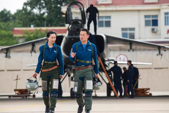 A female pilot assigned to a brigade of the air force under the PLA Northern Theater Command exchange with a male pilot after a flight training exercise in east China's Shandong Province. (Photo/eng.chinamil.com.cn)