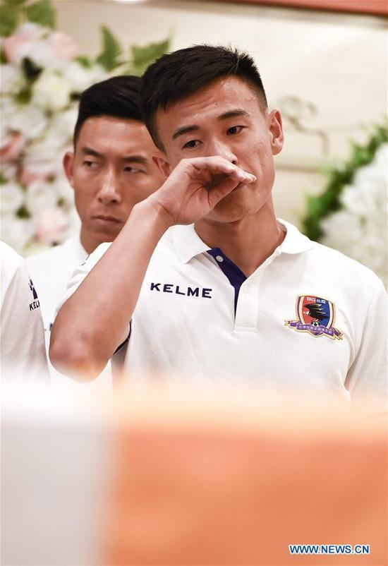 Soccer player Li Xiang (R) of Beijing Enterprises attends the funeral of Cheick Tiote at the Babaoshan funeral center in Beijing, capital of China, June 13, 2017. Cheick Tiote died in hospital after fainting at the Beijing Enterprises club's training ground on June 5, 2017. (Xinhua/Xia Yifang)