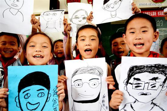 Students of Qiyi Primary School show their paintings to greet the upcoming Father's Day in Yuanqu County, north China's Shanxi Province, June 15, 2017. (Xinhua/Cui Songliang)