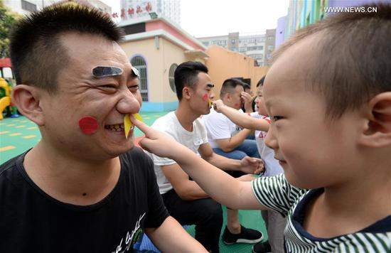 Children play with their father to greet the upcoming Father's Day in Handan City, north China's Hebei Province, June 15, 2017. (Xinhua/Hao Qunying)