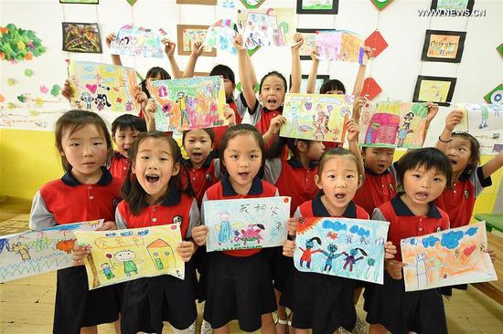 Children show paintings to greet the upcoming Father's Day in Donghai County of Lianyungang, east China's Jiangsu Province, June 15, 2017. (Xinhua/Zhang Zhengyou)