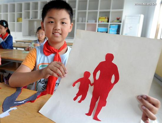A student makes a gift for his father to greet the upcoming Father's Day in Suzhou City, east China's Jiangsu Province, June 15, 2017. (Xinhua/Hang Xingwei)
