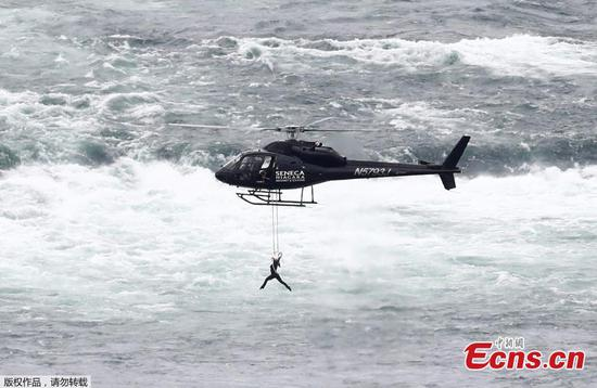 Trapeze artist Erendira Wallenda performs as she hangs from a helicopter flying over the American side of Niagara Falls, in Niagara Falls, Ontario, Canada June 15, 2017. The artist successfully hung twice by her teeth in between hanging upside-down by her toes from a helicopter, breaking record set by her husband (Photo/Agencies)