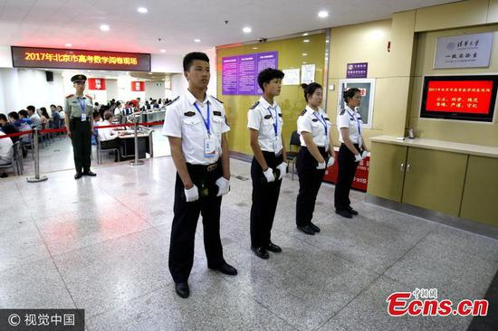 An armed police officer stands guard as teachers undergo strict security checks before they mark papers of the national college exam, or gaokao, at Tsinghua University in Beijing, June 15, 2017. Beijing has improved security checks to ensure fairness, banning teachers from carrying cellphones or other digital equipment when they grade test papers. (Photo/VCG)