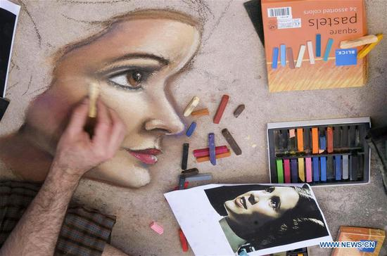 An artist works on a portrait of Star Wars movie character Princess Leia during the 25th annual Pasadena Chalk Festival in Los Angeles, the United States, June 18, 2017. Hundreds artists used more than 25,000 sticks of pastel chalk to create life-size murals on the city pavement. (Xinhua/Zhao Hanrong)