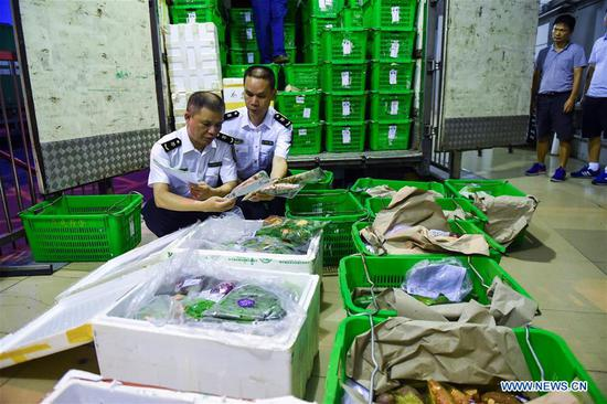 Inspection and quarantine staff members check the goods at Wenjindu Port in Shenzhen, south China's Guangdong Province, June 16, 2017. According to statistics by local authorities, over 85 percent of vegetable, fruit and live poultry from China's inland to Hong Kong markets were transported through the Wenjindu Port of Shenzhen. (Xinhua/Mao Siqian)