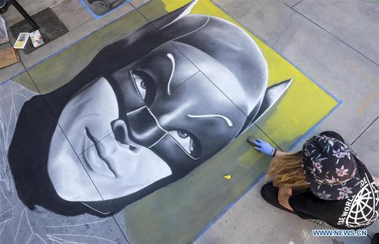 An artist works on a portrait of movie character Batman during the 25th annual Pasadena Chalk Festival in Los Angeles, the United States, June 18, 2017. Hundreds artists used more than 25,000 sticks of pastel chalk to create life-size murals on the city pavement. (Xinhua/Zhao Hanrong)