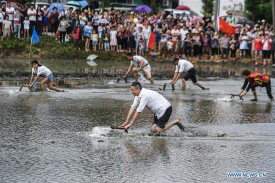 Farmers compete in pushing wooden stools in the paddy fields at an entertainment sports meeting in Lianyang Village of Huzhou City, east China's Zhejiang Province, June 18, 2017. (Xinhua/Xu Yu)