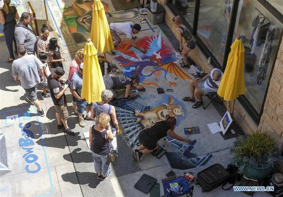 Artists work on their pieces during the 25th annual Pasadena Chalk Festival in Los Angeles, the United States, June 18, 2017. Hundreds artists used more than 25,000 sticks of pastel chalk to create life-size murals on the city pavement. (Xinhua/Zhao Hanrong)