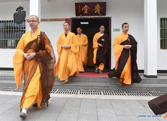 Monks walk out of dining hall at Mount Jiuhua Buddha College, east China's Anhui Province, June 15, 2017. Mount Jiuhua Buddha College was founded in 1990. (Xinhua/Guo Chen)
