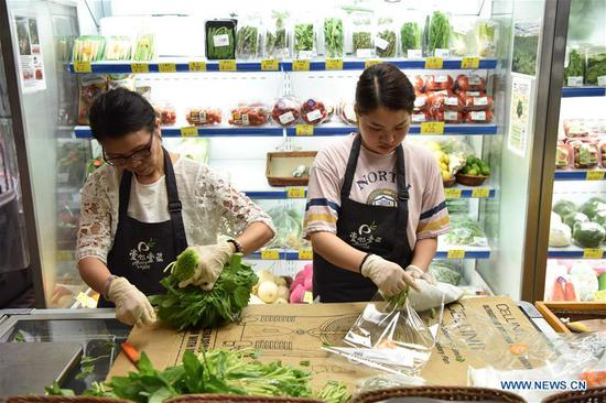 Shopkeepers pack edible amaranth in Hong Kong, south China, June 17, 2017. According to statistics by local authorities, over 85 percent of vegetable, fruit and live poultry from China's inland to Hong Kong markets were transported through the Wenjindu Port of Shenzhen. (Xinhua/Lui Siu Wai)