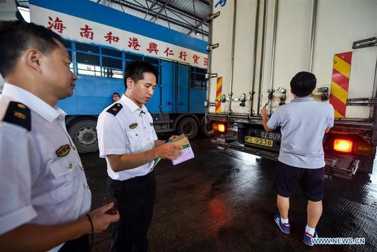 Inspection and quarantine staff members check the bill of goods at Runfeng vegetable trade center in Dongguan, south China's Guangdong Province, June 16, 2017. According to statistics by local authorities, over 85 percent of vegetable, fruit and live poultry from China's inland to Hong Kong markets were transported through the Wenjindu Port of Shenzhen. (Xinhua/Mao Siqian)