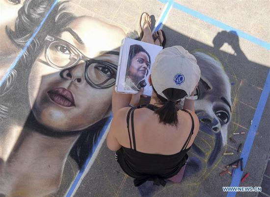 An artist works on her piece during the 25th annual Pasadena Chalk Festival in Los Angeles, the United States, June 18, 2017. Hundreds artists used more than 25,000 sticks of pastel chalk to create life-size murals on the city pavement. (Xinhua/Zhao Hanrong)