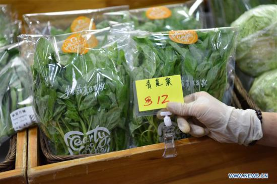 A shopkeeper prepares the price tag for packed edible amaranth in Hong Kong, south China, June 17, 2017. According to statistics by local authorities, over 85 percent of vegetable, fruit and live poultry from China's inland to Hong Kong markets were transported through the Wenjindu Port of Shenzhen. (Xinhua/Lui Siu Wai)