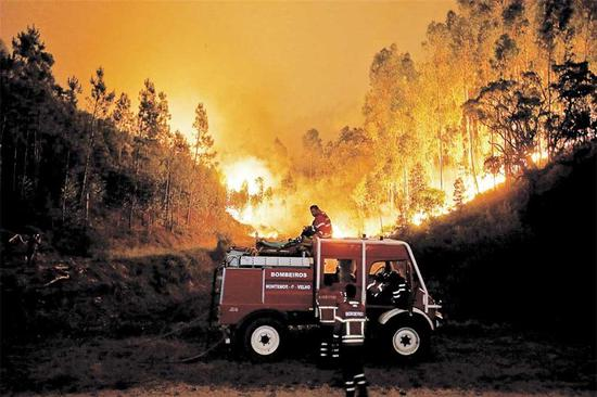 Firefighters battle a forest blaze near Bouca, central Portugal, yesterday. At least 62 people have ied in the fires, most burned to death in their cars.