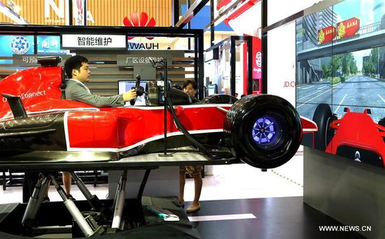 A visitor experiences a driving simulator at the exhibition area of Chinese telecom giant Huawei during the first World Intelligence Congress in Tianjin, north China, June 29, 2017. The congress opened here on Thursday. (Xinhua/Zhang Yudong)