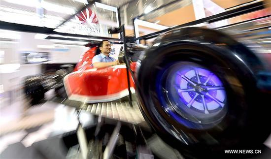 A visitor experiences a driving simulator at the exhibition area of Chinese telecom giant Huawei during the first World Intelligence Congress in Tianjin, north China, June 29, 2017. The congress opened here on Thursday. (Xinhua/Yue Yuewei)
