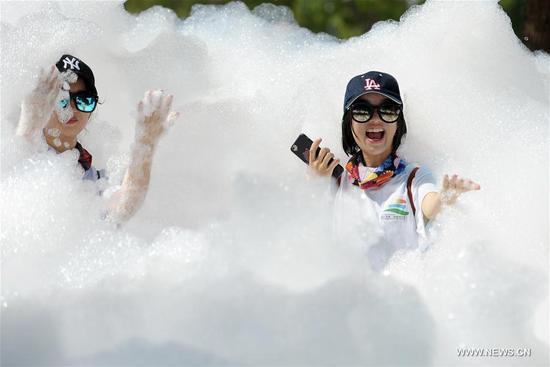 Two girls play amid foam during an event of Rainbow Bubble Run in Zhoushan, east China's Zhejiang Province, July 9, 2017. (Xinhua/Wu Linhong)