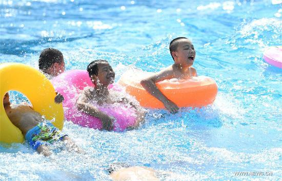 Kids played in water to keep cool in a water park in Chongqing, July 11, 2017. An orange level high temperature warning is issued by the meteorological observatory of southwest China's Chongqing Municipality Tuesday. (Xinhua/Wang Quanchao)